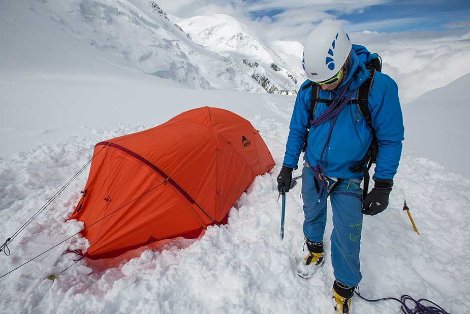 mountaineer standing outside of tent