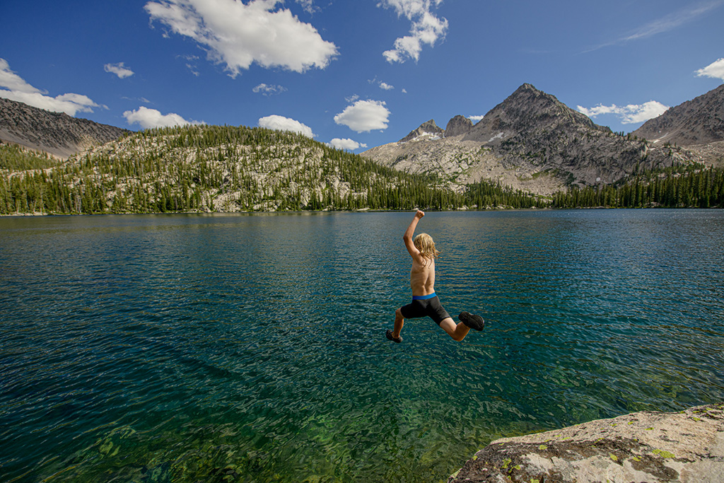10 yo. Jasper Lee-Meyers launches off a rock into Toxaway Lake on a backpack along the Toxaway/Alice Lakes loop. Sawtooth Wilderness, Idaho.