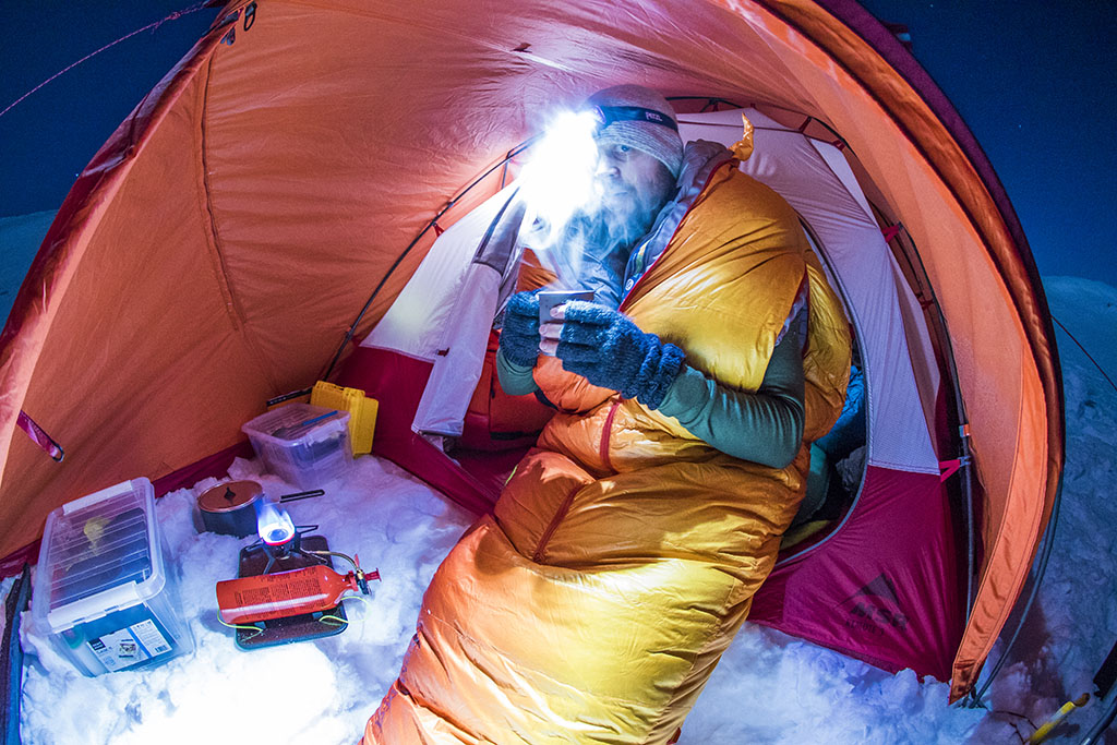 eating dinner at night in mountaineering tent